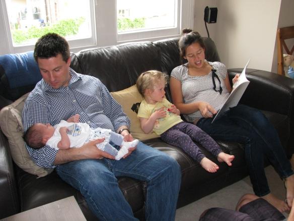 Shoshanna's brother Jonny holding Henry while Helen reads Amaya a story.